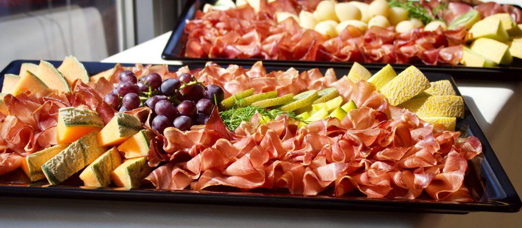 Gemischte Schinkenplatte, u. a. garniert mit Melonen und Trauben.